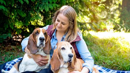 A woman cuddling two dogs.