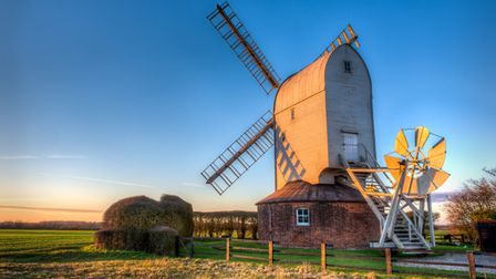 Aythorpe Roding, Essex: A picture-perfect white windmill in the sunset. In the distance: flat countryside.