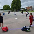 Children dance on a measured and painted socially distanced circle in the playground as they wait to