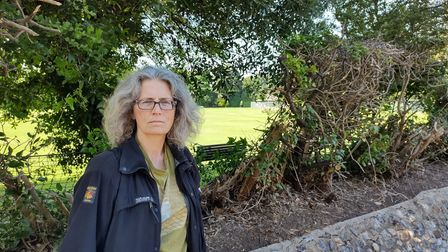 Overstrand wildlife campaigner Maggie Wilcox in front of the netting and hedgerow.