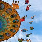 A fair ground ride where people sit in hanging chairs and whirl in a circle