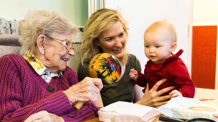 baby making friends with elderly person