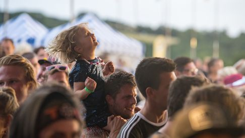 A crowd watches an event on stage, a child dances to the music on his parent's shoulders