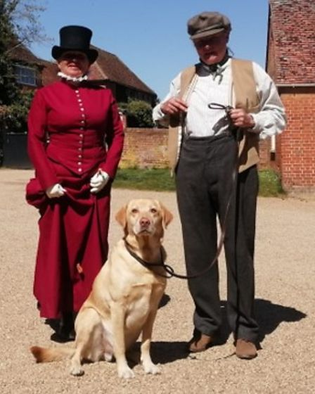 A dog called Jack standing between two people