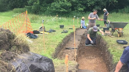 A long muddy trench with a group of people at the other end - The archaeological dig at Clavering Castle