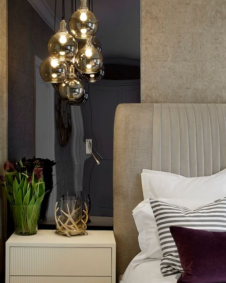 Modern bedroom accessorised with lighting, vases, pillows and candles, designed by Juliettes Interiors in Chelsea.