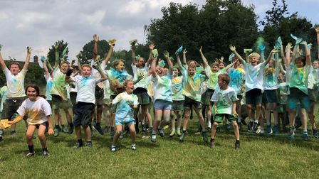 Children with tops coated in multiple colours after a colour run at R A Butler Academy, Saffron Walden, Essex
