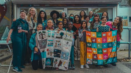 Little Handersand Team LHD at the end of the festival, holding the textile community project SDG Squarewall hanging