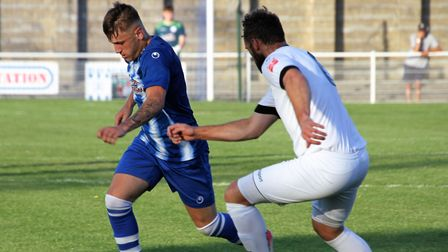 Clevedon Town's Ethan Feltham takes on Weston's Sam Avery