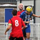 Clevedon Town's Syd Camper heads clear from Clevedon United's Joe Teall