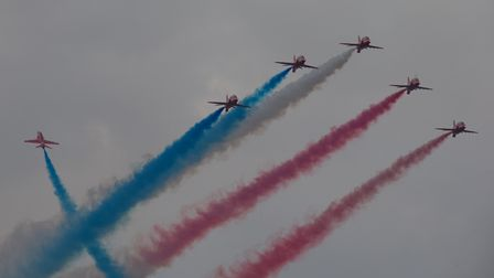 The Red Arrows fly back towards Duxford, nose lights and coloured smoke both activated, at the Duxford Summer Air Show.