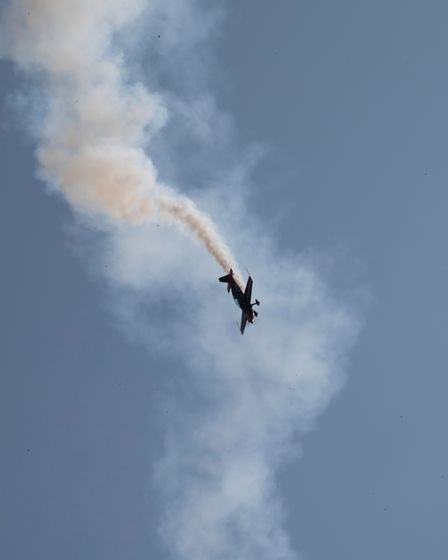 An Extra 300, part of The Blades display group, performs a vertical manoeuvre at the Duxford Summer Air Show.