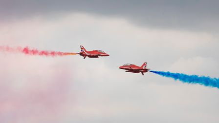 Two members of the Red Arrows perform a manoeuvre, crossing each other in the centre of the airfield, at IWM Duxford