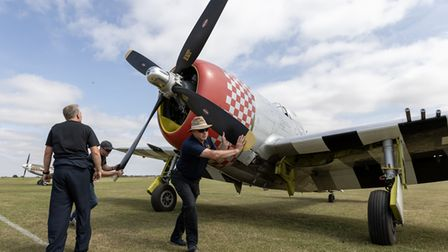 A crew work on the propeller of a Mustang at the Duxford Summer Air Show at IWM Duxford.