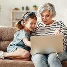 Happy aged woman with cute granddaughter smiling while sitting on sofa and using laptop in living r