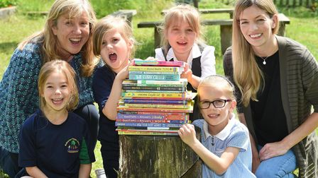 Staff and pupils Mulbarton Primary School with some of the donated books worth hundreds of pounds.
