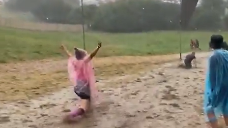 A woman in a poncho with her hands in the air on a very muddy hill