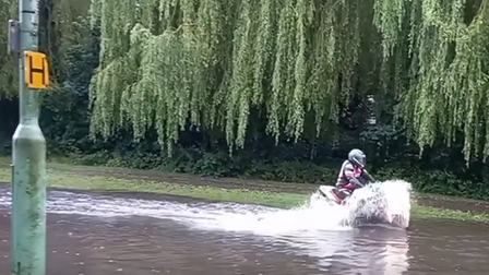 A road in Haverhill looks more like a river. A person on a motorbikes rides through, creating a splash.