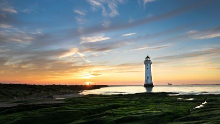 Sunset image of New Brighton lighthouse or Perch Rock which is situated on the River Mersey and Liv