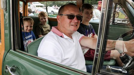 Four people - three children and an adult, David - in a shiny Morris Minor