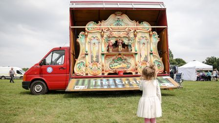 A little girl aged three wearing a white dress, Louella, in front of a large, cream-coloured musical van