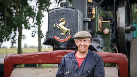 A man wearing a cap, Adrian, in front of a large vintage steam roller in Debden