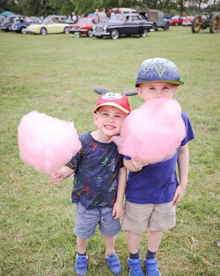 Two boys - Eli and Issac - enjoy large cloud of candy floss on the lawn at Debden, Essex