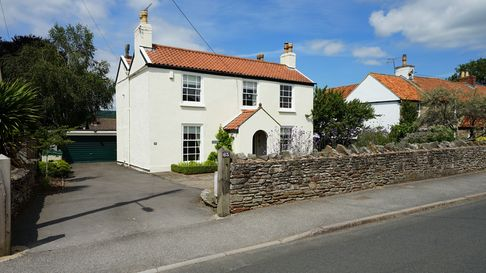 cream rendered double-fronted house with gabled porch, side driveway leading to double garage and stone wall in front
