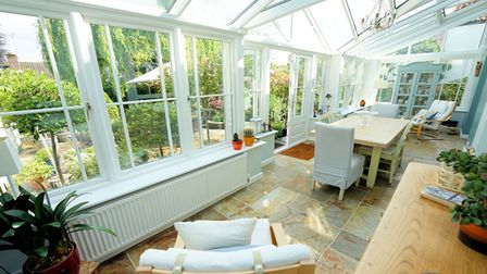 large conservatory overlooking garden with long under-window radiator, tiled flooring, table and chairs, sideboard