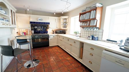 kitchen with flagstone floor, cream units, tiled worktops, dishwasher, range cooker at far end, plate shelves and glass table