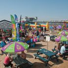 weston-super-mare beach on a sunny bank holiday with gift shop and picnic tables in foreground and grand pier on the right