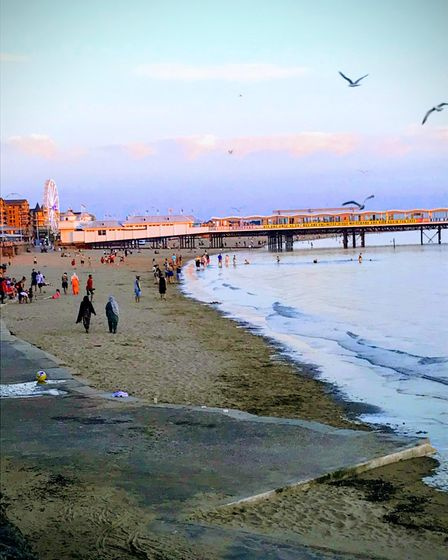 dusk shot of Weston-super-Mare with people walking along the shoreline and The Grand Pier in the background