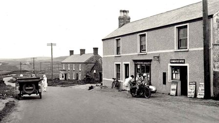 An old image of a motorbike outside of Sennen Post Office