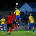 Scott Piper of Torquay United wins the aerial challenge against Trialist of Truro City during the p