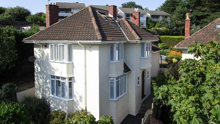 corner view of cream-rendered detached house with windows on front and side and trees in front, in Hill Road, Weston