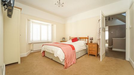 double bedroom with cream walls, white corniced ceiling with light fitting, door to right, wardrobe on left and beige floor