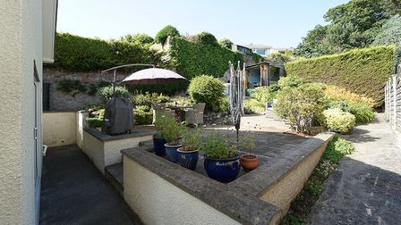 paved garden at back of property, with stone walls, pots with plants, shrubs, washing line, freestanding parasol and hedging