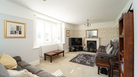living room with grey wall and wallpapered wall, white cornice above, cream floor, bay window on left with white blinds