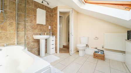 modern bathroom with P-shaped bath with shower panel on left, beige tiled wall behind, sink, cupboards, toilet and roof light