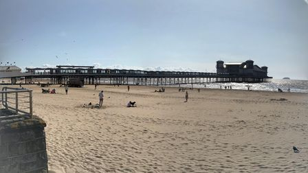 Weston's sandy beach with The Grand Pier in the background, the tide coming in and a few people dotted about