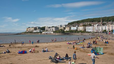 People bathing and enjoying Marine Lake, in Weston-super-Mare, on a sunny day, with Madeira Cove in the background