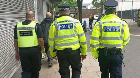 A council enforcement officer with two police officers