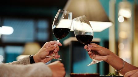 People clinking glasses with red wine