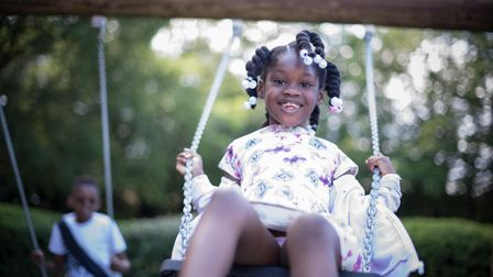 Young girl plays on the swing