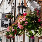 old pub with floral display outside