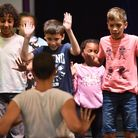 Rosy May and the children of ACYCLE performing a dance to celebrate the end of their year in the project