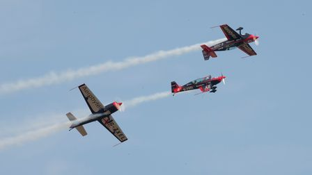 Three pilots from The Blades, flying in Extra 300s, perform a display at the Duxford Summer Air Show