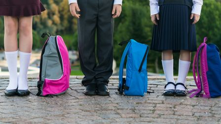 Schoolchildren with backpacks stand in the park ready to go to school, long photo