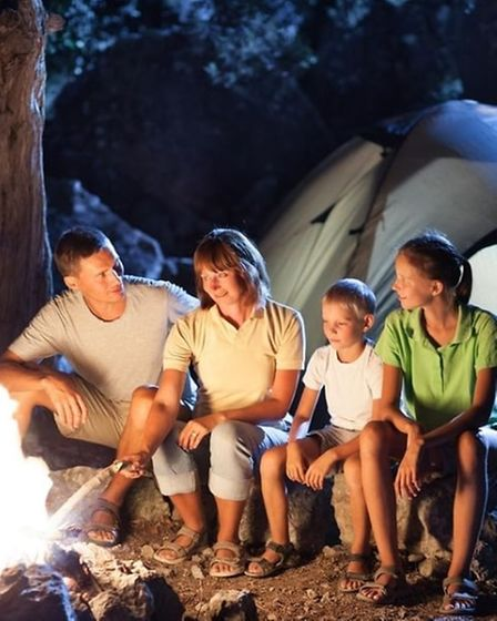 A family sitting in front of a fire pit.