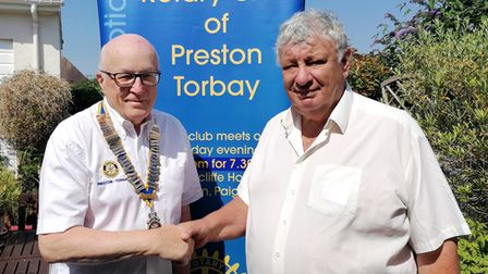 Roger Tisdall, right, hands over the chains of office to incoming Preston Rotary Club president Mike Ford.